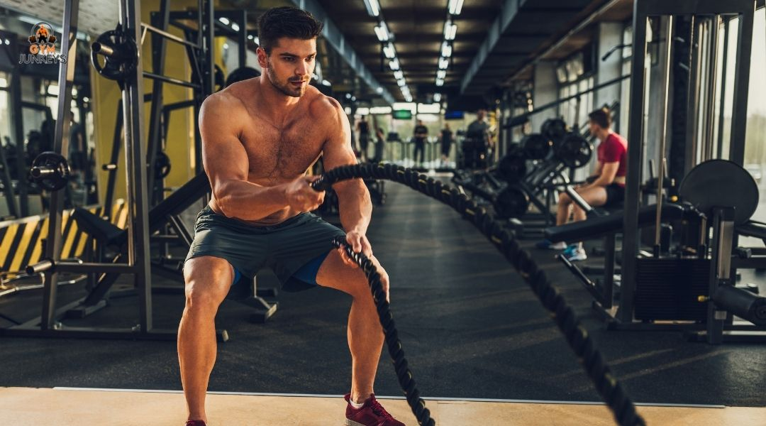 man working out in a gym with ropes