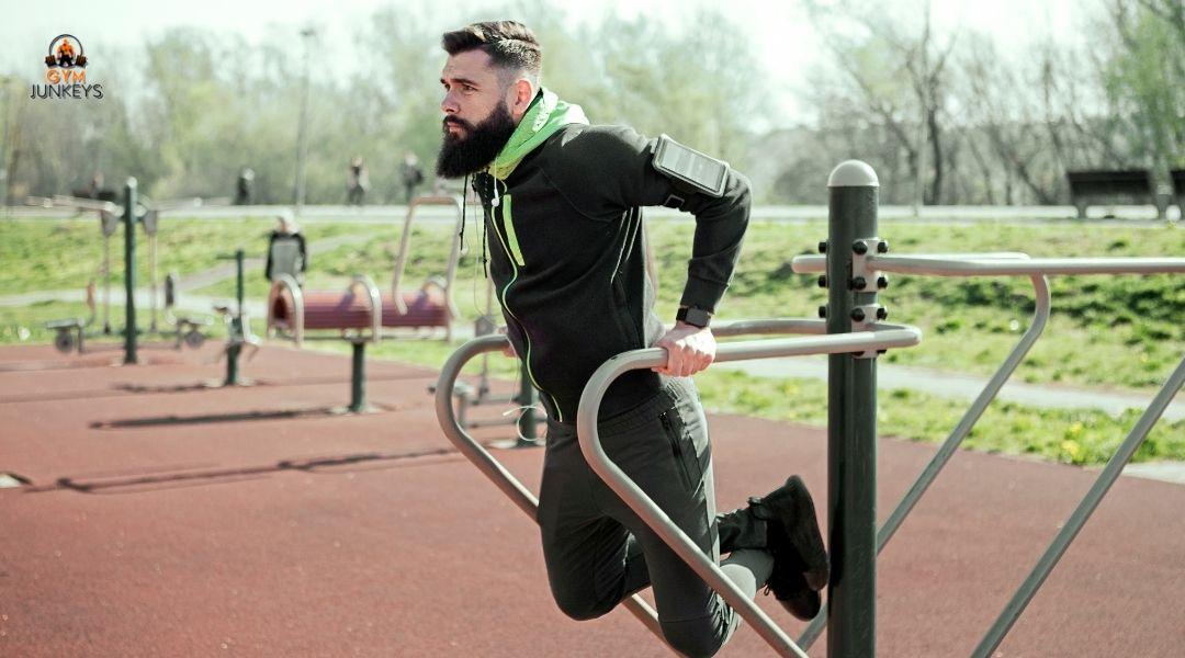 man doing a tricep dip at a workout park